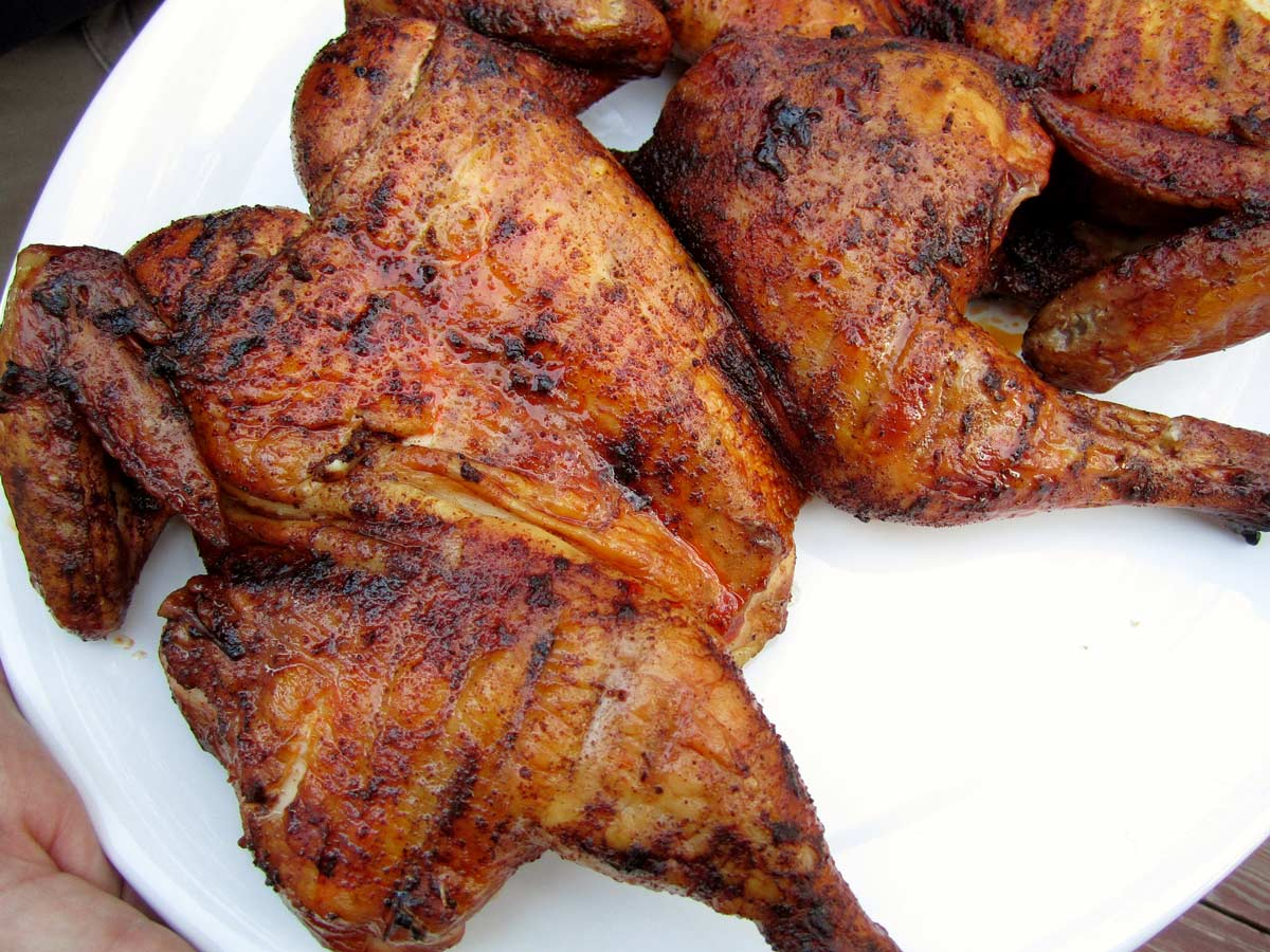 Closeup of a smoked spatchcock chicken on a white platter.