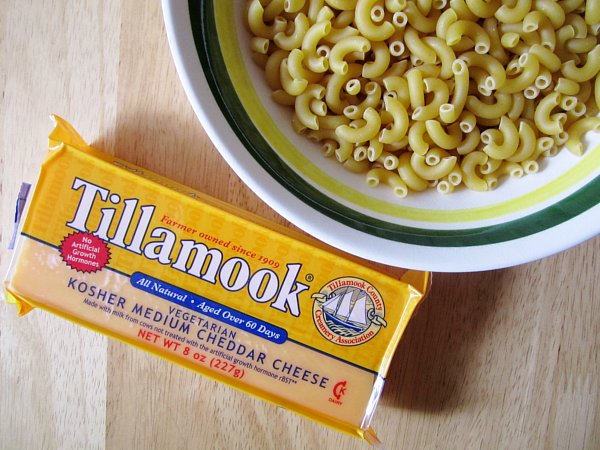 A bowl of uncooked elbow macaroni and a block of Tillamook cheddar cheese