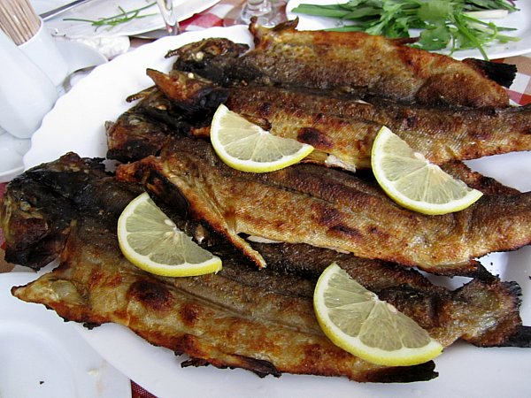 a platter of whole cooked fishes topped with lemon slices