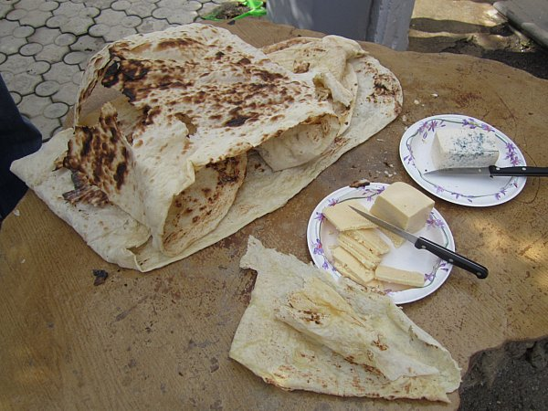 piles of lavash flatbread and plates of cheese on a wooden table