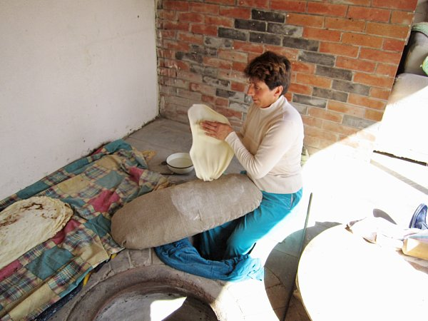 a woman sitting on the ground stretching a piece of dough between her hands