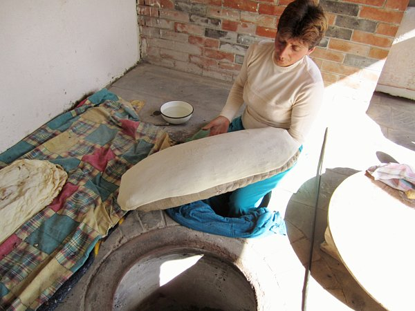 a woman sitting on the ground stretching a piece of dough over a large pillow