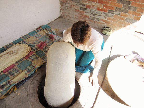 a woman sitting on the ground holding a large pillow lined with dough