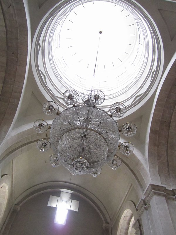 view looking up at a chandelier in a church