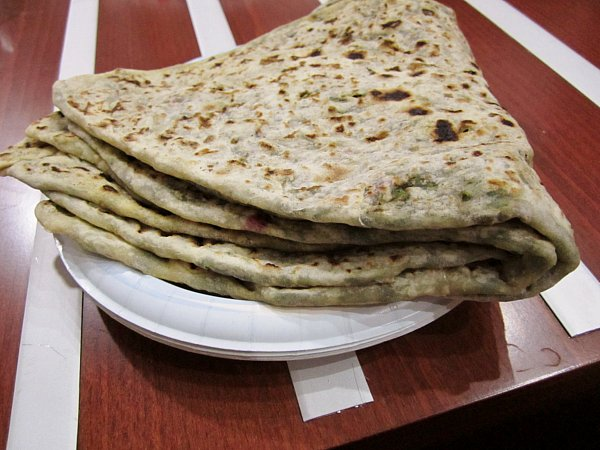 a stack of flatbread on a white plate