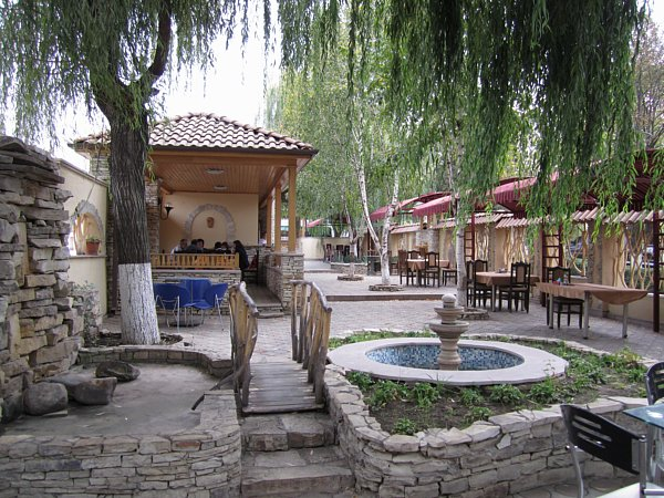 an outdoor garden space with a small fountain, tables and chairs