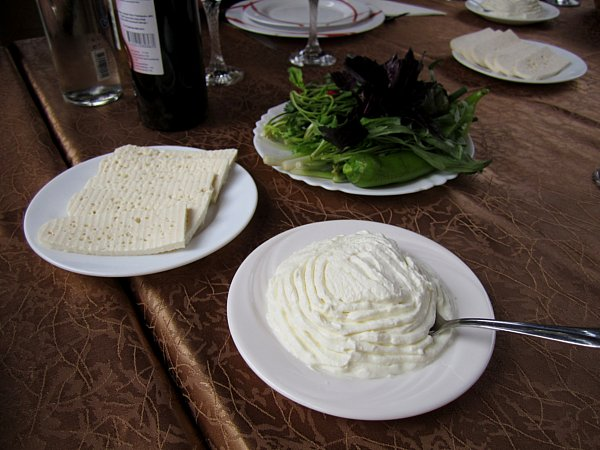 plates of cheese, strained yogurt, and herbs on a brown table