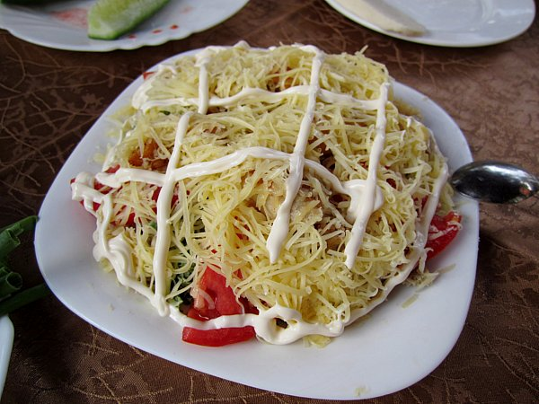 A plate of food topped with shredded cheese and white sauce