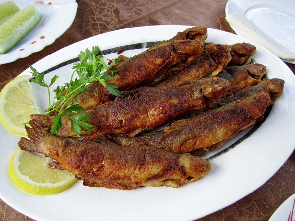 fried fishes on a white platter on a brown table