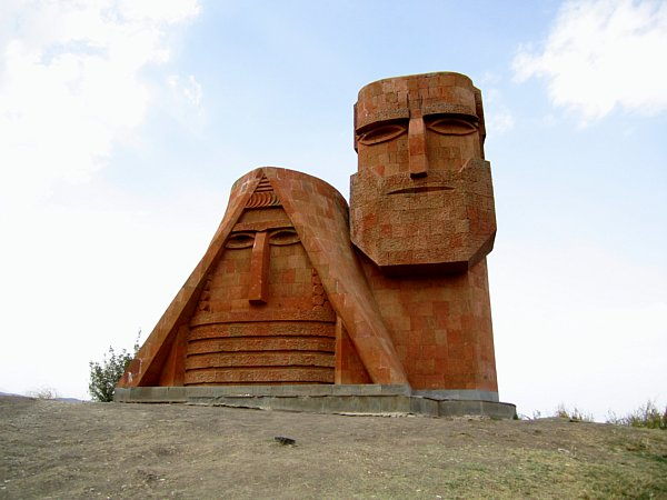 a red stone statue resembling a man and woman