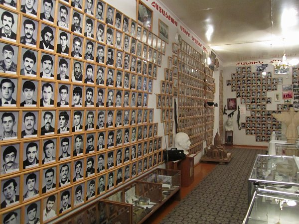 a room lined with framed photos of people on the walls