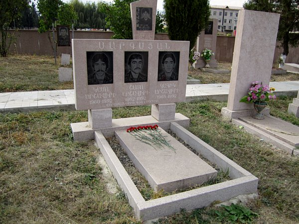 A grave with photos of three people on the gravestone