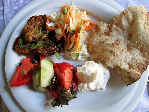 A plate of food with bread, vegetables, and strained yogurt