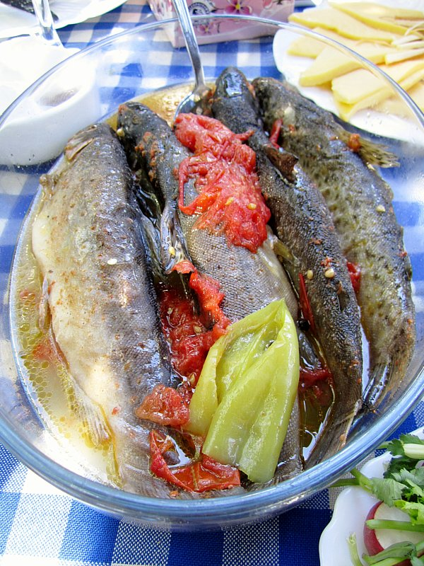 an oval glass platter filled with cooked fish