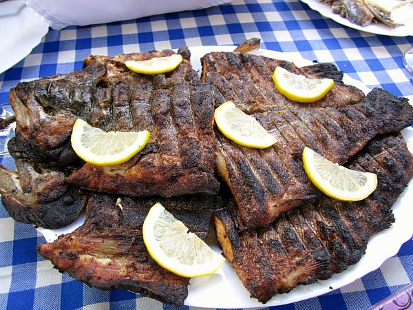 grilled pieces of fish on a white plate on a blue and white checkerboard tablecloth