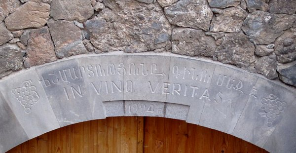 an engraved stone sign that says In Vino Veritas