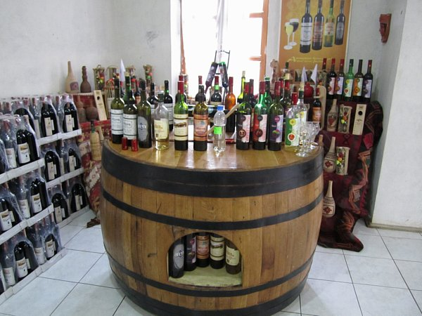wide view of a wooden table resembling a wine barrel topped with bottles of wine