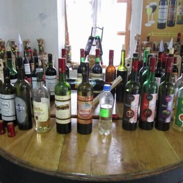 a row of wine bottles on a wooden surface