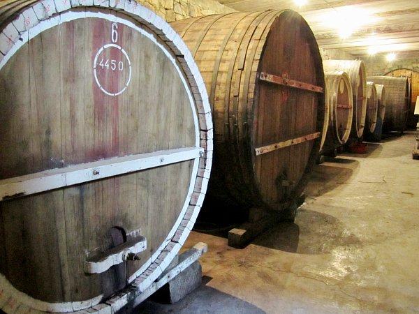 a closeup of wine barrels lining a wall