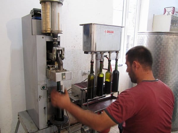 A man standing in front of a machine filling bottles with wine