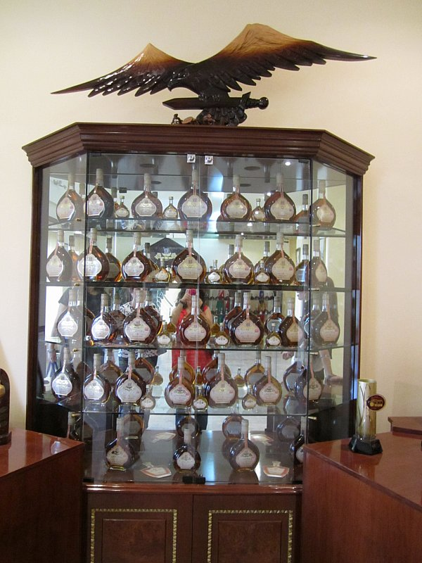a glass enclosed display filled with bottles of Armenian brandy