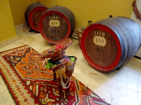 alcohol barrels with a figure of a camel standing in front on a colorful rug