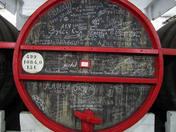 an alcohol barrel with lots of chalk writing on its surface