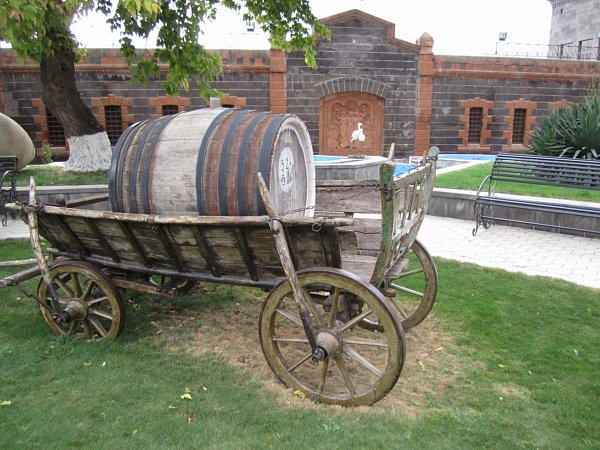 a wooden carriage topped with a large wooden barrel in front of a stone building