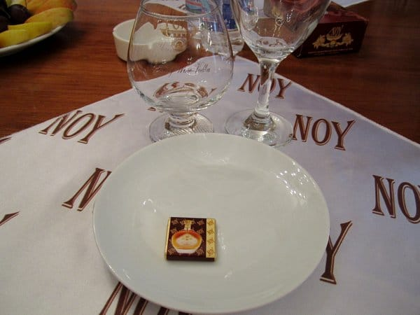A closeup of a place setting on a table with a white plate and glasses