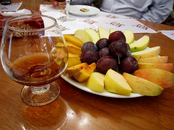 a platter of fruits next to a glass of brandy