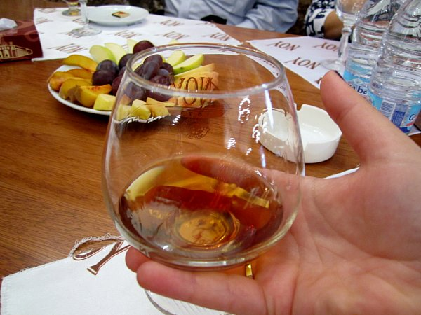 a closeup of a glass of brandy in someone\'s hand