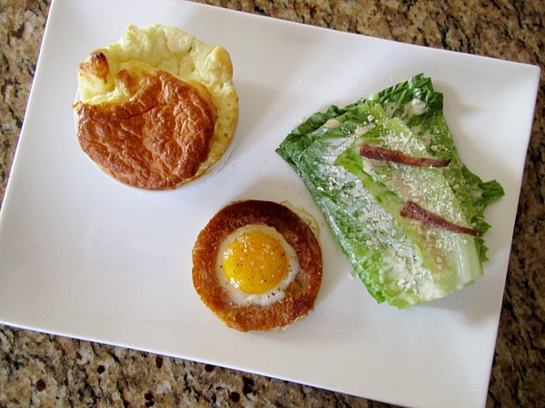 overhead view of a cheese souffle, round toast filled with an egg, and romaine lettuce