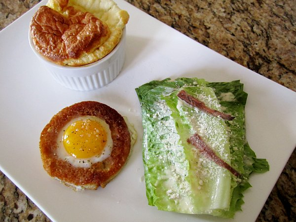 overhead view of a small cheese souffle, round toast filled with egg, and romaine lettuce stack