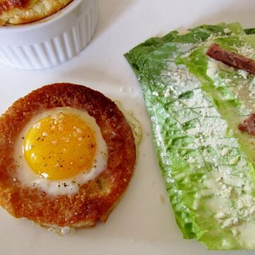 closeup of a round bread toast filled with an egg, and a stack of romaine lettuce