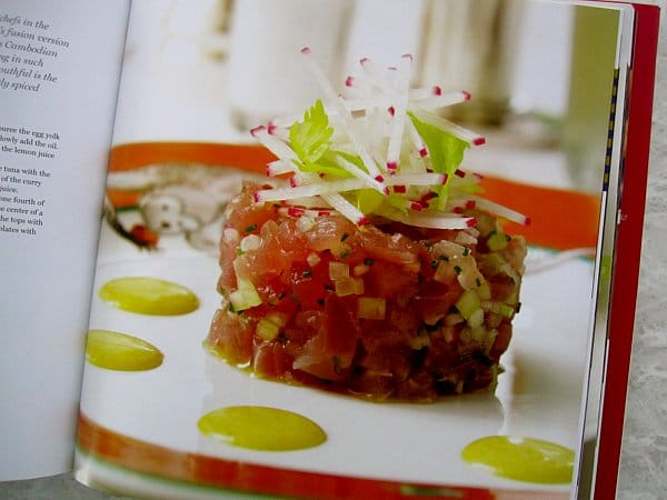 a cylinder of chopped raw tuna with cucumber on a white plate