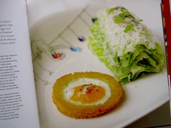 A closeup of a round toast filled with an egg and a stack of romaine lettuce
