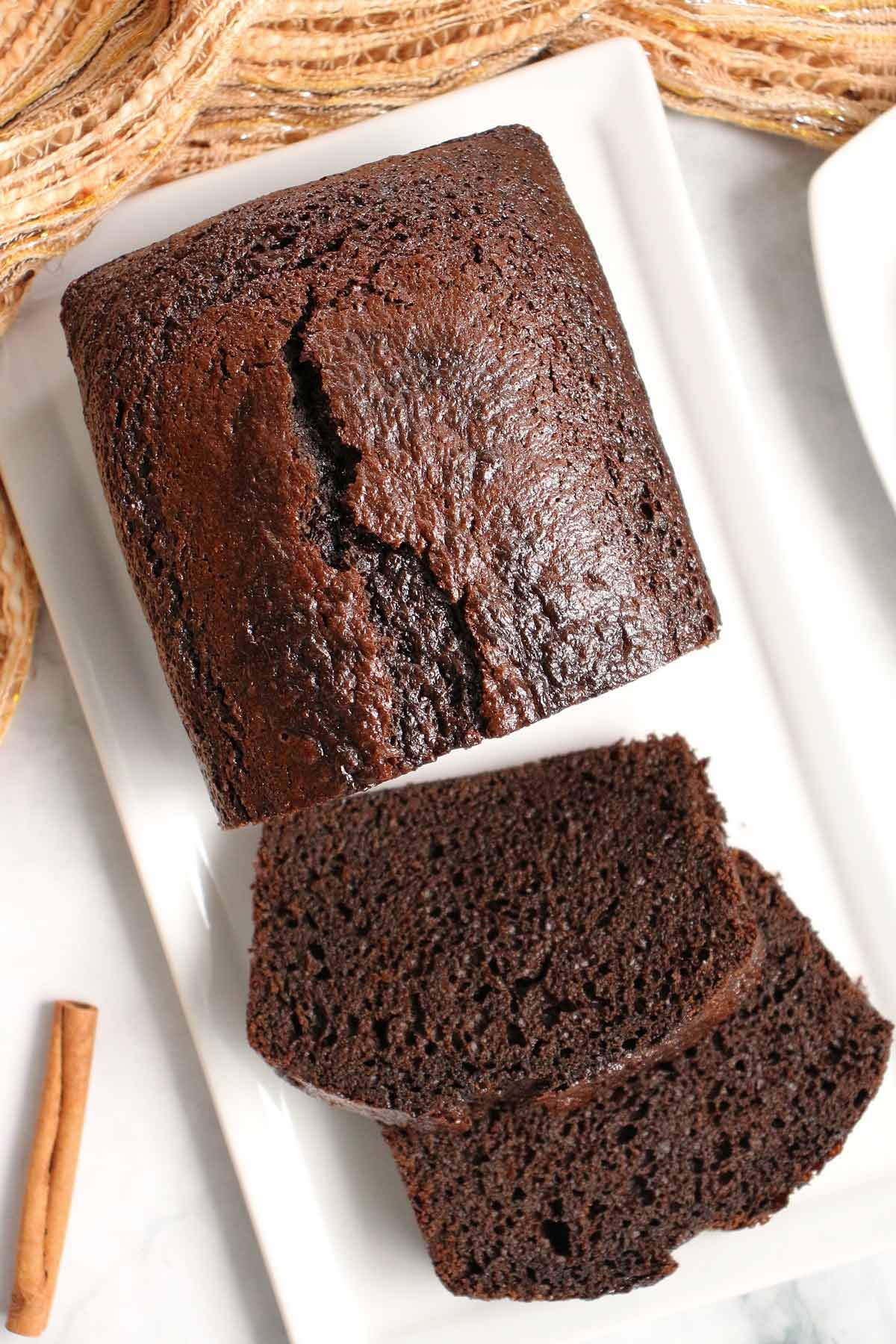 Closeup of a partially sliced loaf of dark brown spice bread on a white rectangular plate.