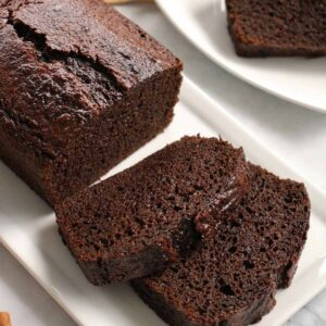 A partially sliced loaf of dark brown gingerbread on a white platter.