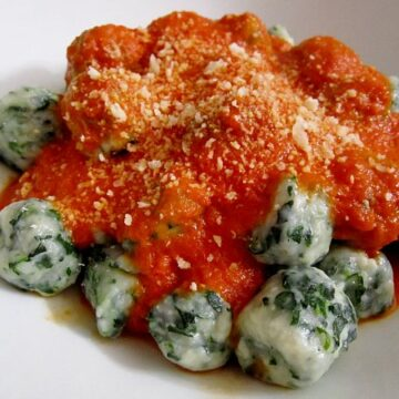 side view of a white plate topped with spinach and ricotto gnudi dumplings with tomato sauce