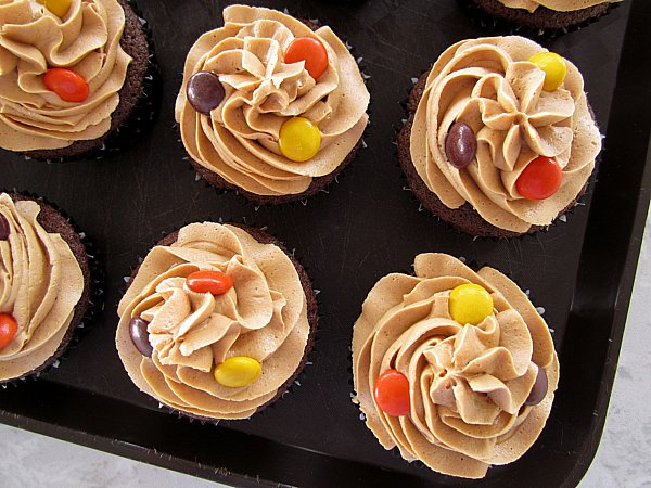 overhead view chocolate cupcakes with peanut butter frosting and Reese\'s Pieces on a black surface