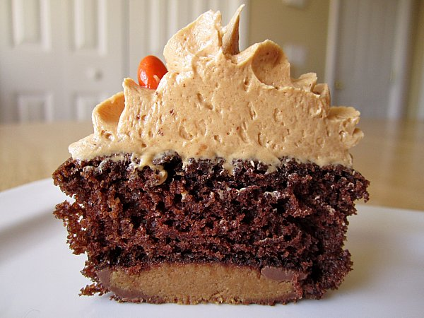 closeup of a cross section of a chocolate cupcake with a peanut butter cup bottom