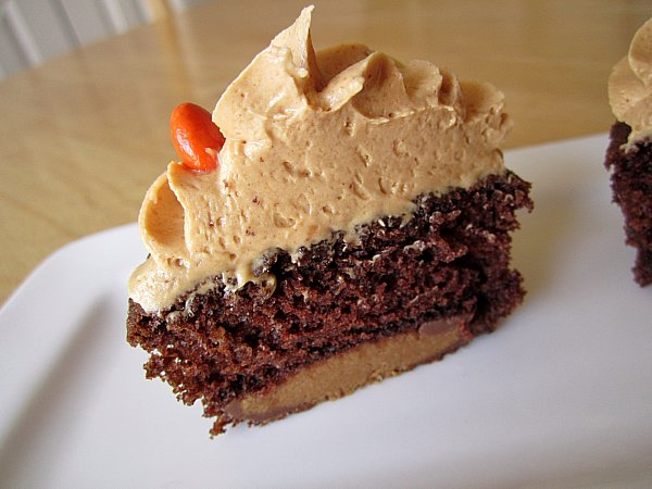 cross section of a chocolate cupcake with a peanut butter cup on the bottom