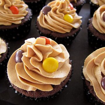 chocolate cupcakes with peanut butter frosting and Reese's Pieces on top on a black surface