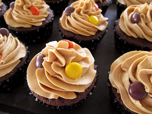 chocolate cupcakes with peanut butter frosting and Reese\'s Pieces on top on a black surface