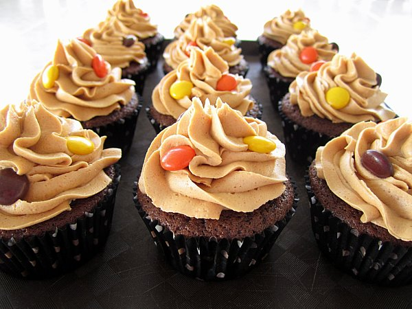 a black tray topped with chocolate cupcakes with peanut butter frosting and Reese's Pieces on top