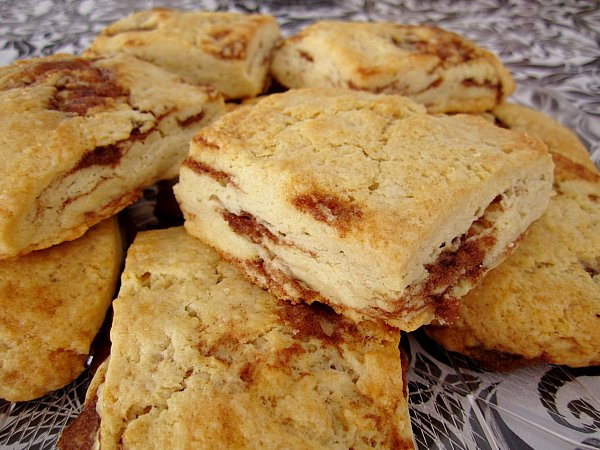 a pile of square cinnamon honey scones on a platter