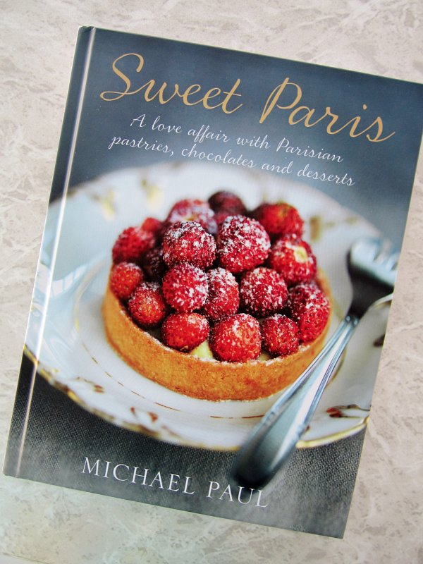 the cover of a cookbook called Sweet Paris with a red berry tart on it