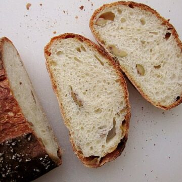 overhead view of two slices of crusty green olive bread on a white surface