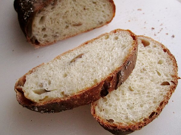 a closeup of two slices of crusty green olive bread on a white surface