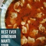 a shallow bowl of manti (Armenian dumplings) in a tomato broth